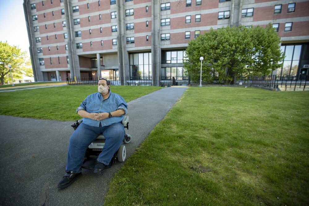 David Underhill sits outside of the Cardinal Medeiros Towers in Fall River. He has been a public housing tenant for 12 years and sits on the town's board of housing commissioners. (Jesse Costa/WBUR)