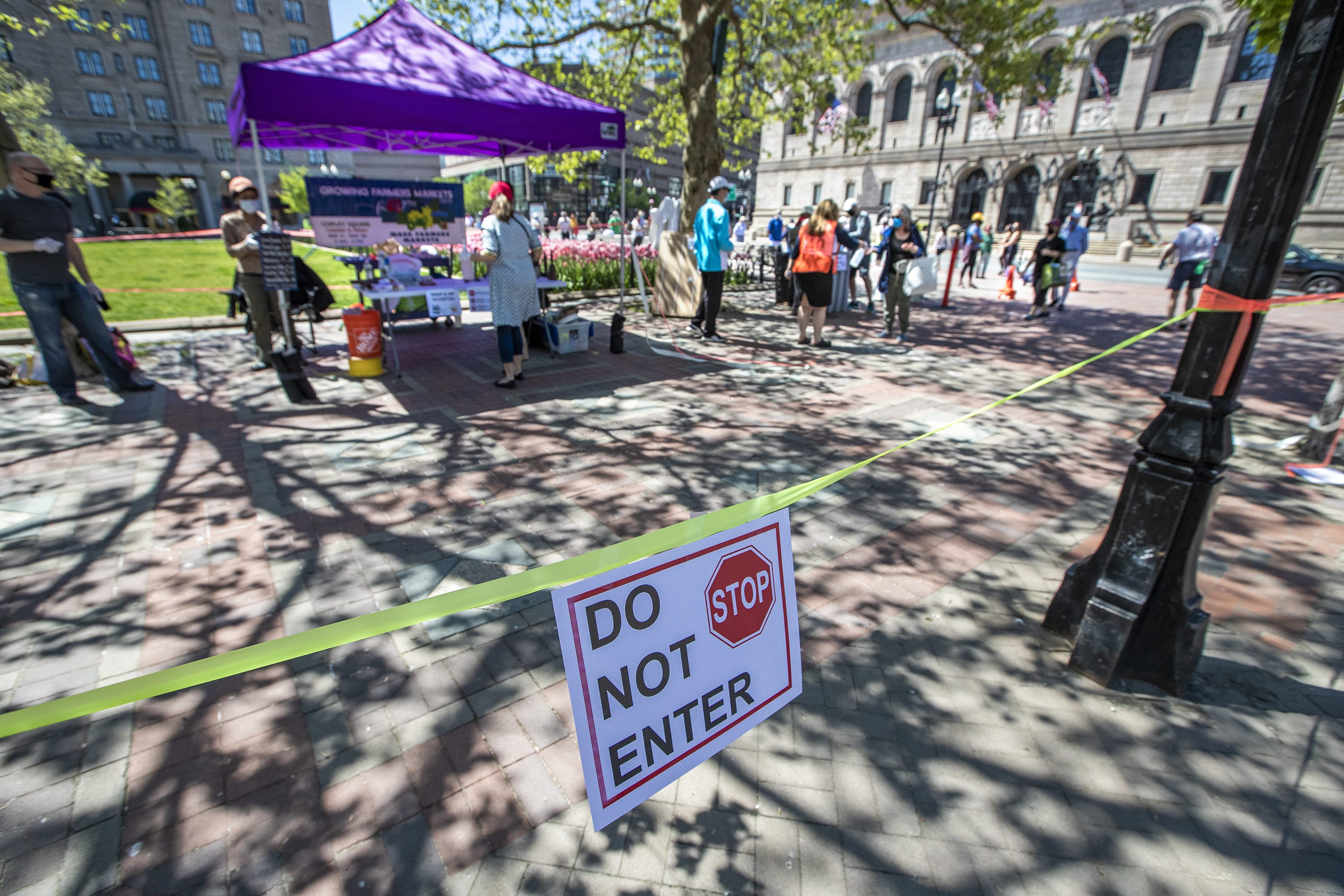 Caution tape surrounds the perimeter of the Copley Square Farmers Market, to keep people entering and exiting through one way, as it got under way Friday. (Jesse Costa/WBUR)