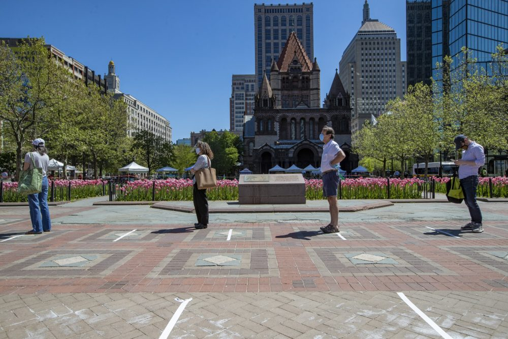 People stand in line, at least six-feet apart, to enter the Copley Square Farmers Market. (Jesse Costa/WBUR)