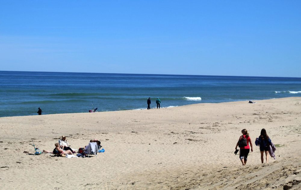 Two people walk along Newcomb Hollow Beach in Wellfleet. (Quincy Walters/WBUR)