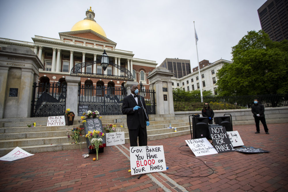 Lewis Elisa of the Boston Black COVID-19 coalition speaks in front of the State House during a protest to honor black people and Latinos who have died of COVID-19. (Jesse Costa/WBUR)