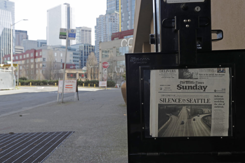 "The street next to a Seattle Times newspaper box in front of the building that houses the Times' newsroom is empty, Sunday, March 15, 2020 in Seattle, as the headline ""Silence in Seattle"" is displayed. (Ted S. Warren/AP Photo)"