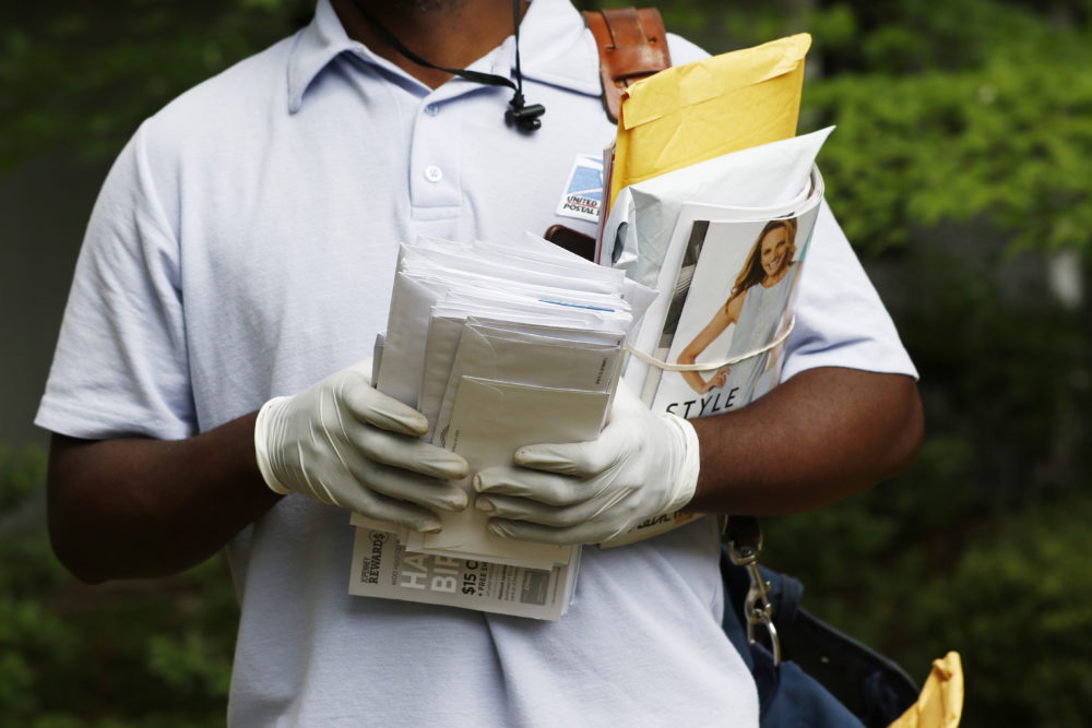 A postal service carrier dons gloves as he delivers mail in northeast Jackson, Miss., Monday, March 30, 2020. The letter carrier, who asked to not be identified, said other carriers in his post office also have started to wear gloves amid concerns for the new coronavirus. (Rogelio V. Solis/AP)