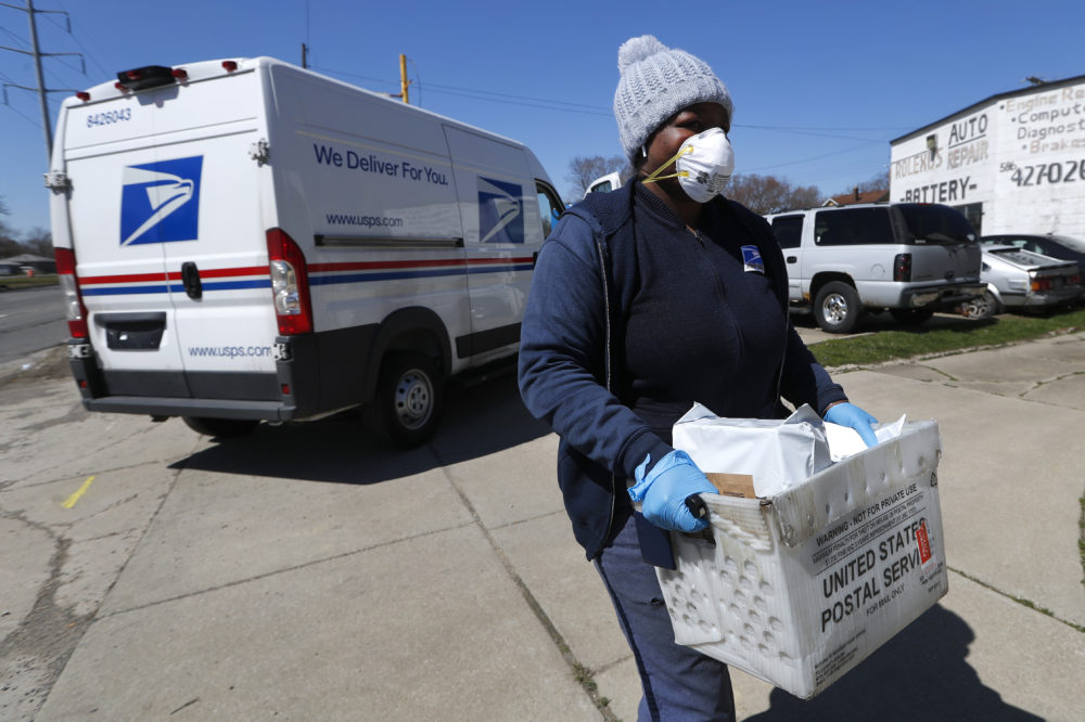 A United States Postal worker makes a delivery with gloves and a mask in Warren, Mich., Thursday, April 2, 2020. The U.S. Postal Service is keeping post offices open but ensuring customers stay at least 6 feet apart. The agency said it is following guidance from public health experts, although there is no indication that the new coronavirus COVID-19 is being spread through the mail. (Paul Sancya/AP)