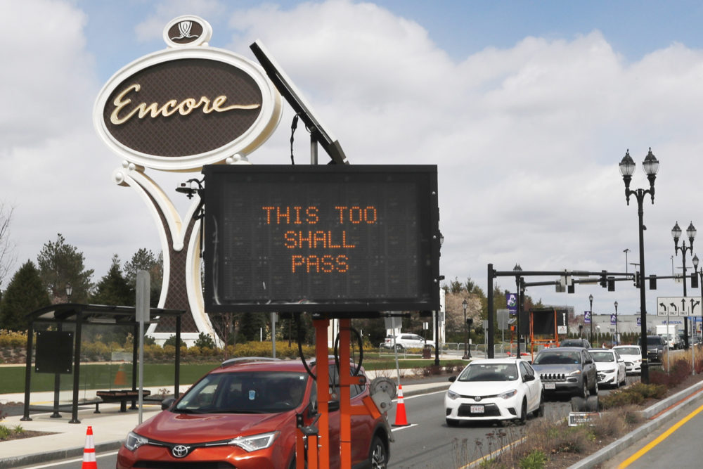 "A roadway sign reads ""THIS TOO SHALL PASS""  as cars pass the entrance leading to the Encore Boston casino in Everett, Mass., April 22, 2020. (Charles Krupa/AP)"