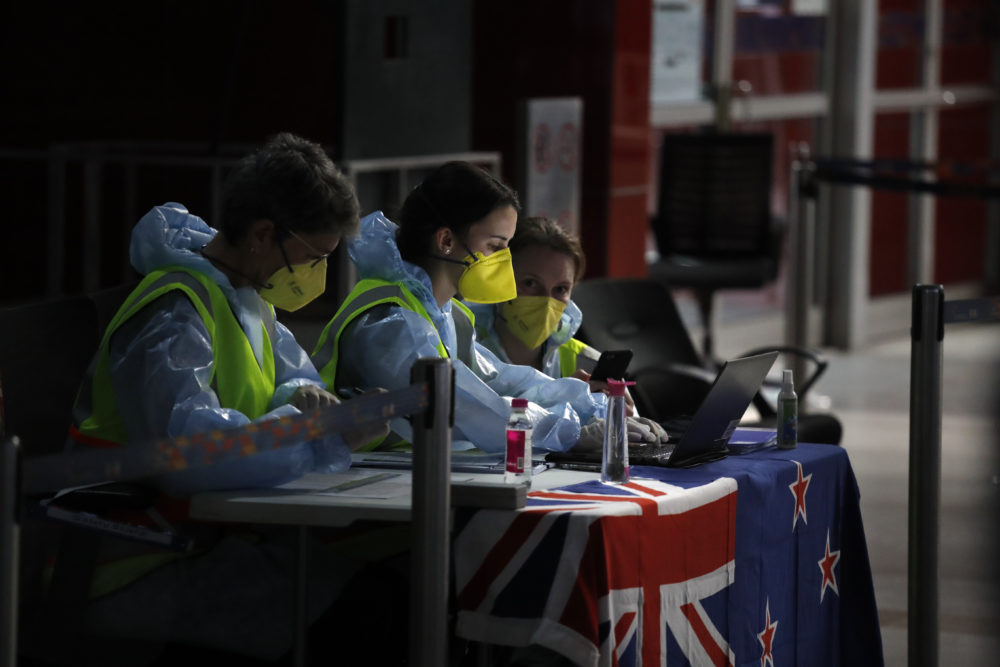 New Zealand officials go through the passengers list as stranded New Zealand nationals arrive to board a repatriation flight back home at the Indira Gandhi International airport in New Delhi, India, Thursday, April 23, 2020. New Zealand has closed the border to everyone except citizens and residents to stop the spread of new coronavirus. (Manish Swarup/AP)
