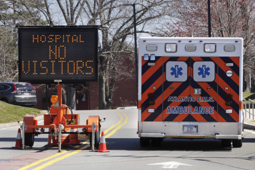 An ambulance rolls pass a sign alerting drivers, that due to the COVID-19 virus outbreak, no visitors are allowed at Essex County's Beverly Hospital in Beverly, Mass., Thursday, April 23, 2020. (Charles Krupa/AP)