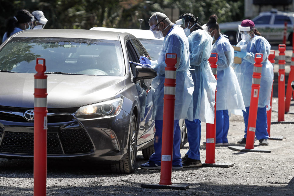Health workers conduct COVID-19 tests at a drive through coronavirus testing site at a community center. (John Raoux/AP)