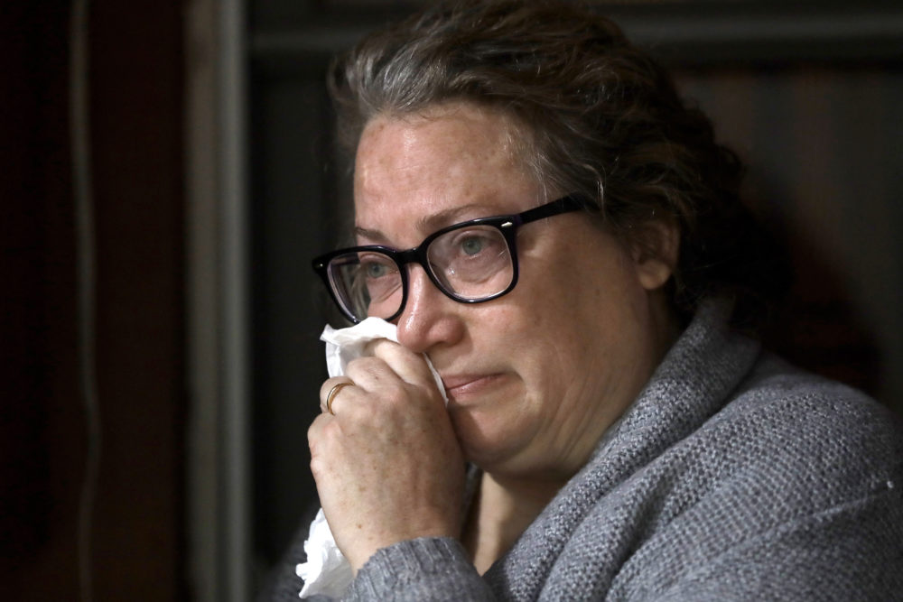 Susan Kenney, of Ware, Mass., who lost her father to the coronavirus, is tearful while speaking to a reporter from The Associated Press on the front porch of her home in Ware. (Steven Senne/AP)