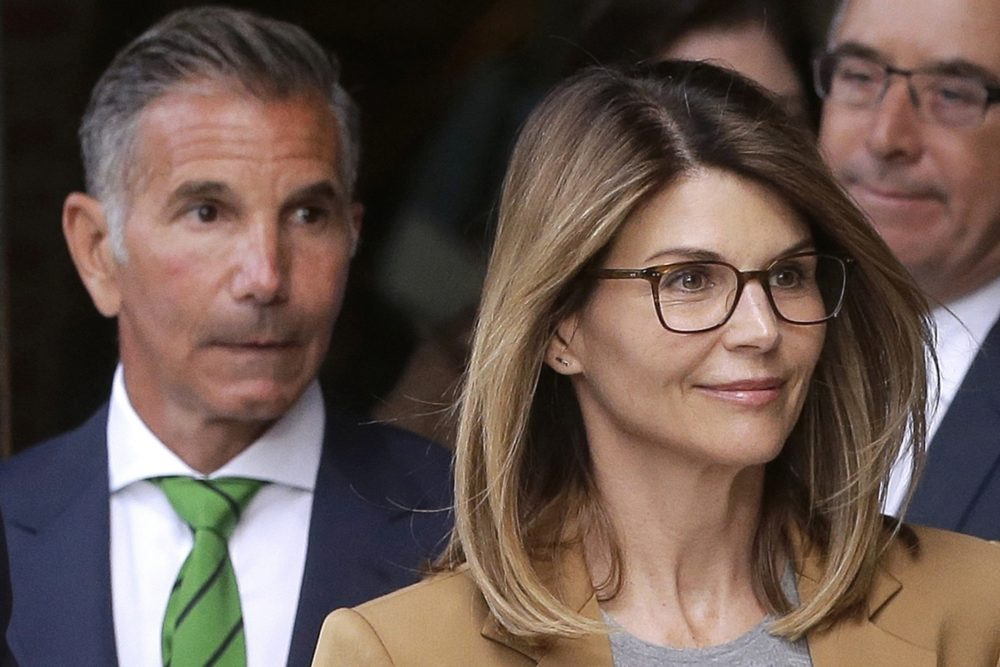 FILE - In this April 3, 2019, file photo, actress Lori Loughlin, front, and her husband, clothing designer Mossimo Giannulli, left, depart federal court in Boston after a hearing in a nationwide college admissions bribery scandal. (Steven Senne/AP File)