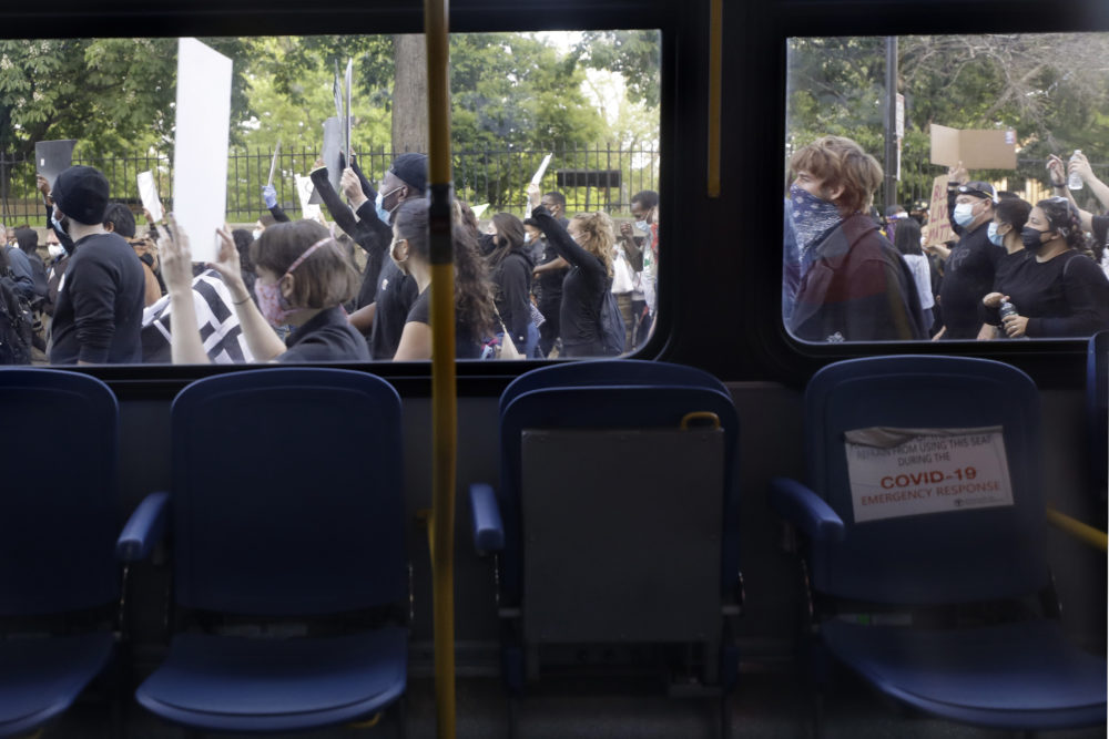 Protesters walk past an empty bus as they demonstrate Sunday, May 31, 2020, in Boston, over the death of George Floyd. (Steven Senne/AP Photo)