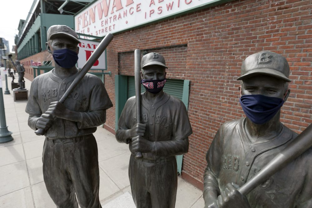 Statues of former Boston Red Sox greats, from left, Ted Williams, Bobby Doerr and Johnny Pesky, wear protective masks outside Fenway Park. (Michael Dwyer/AP)