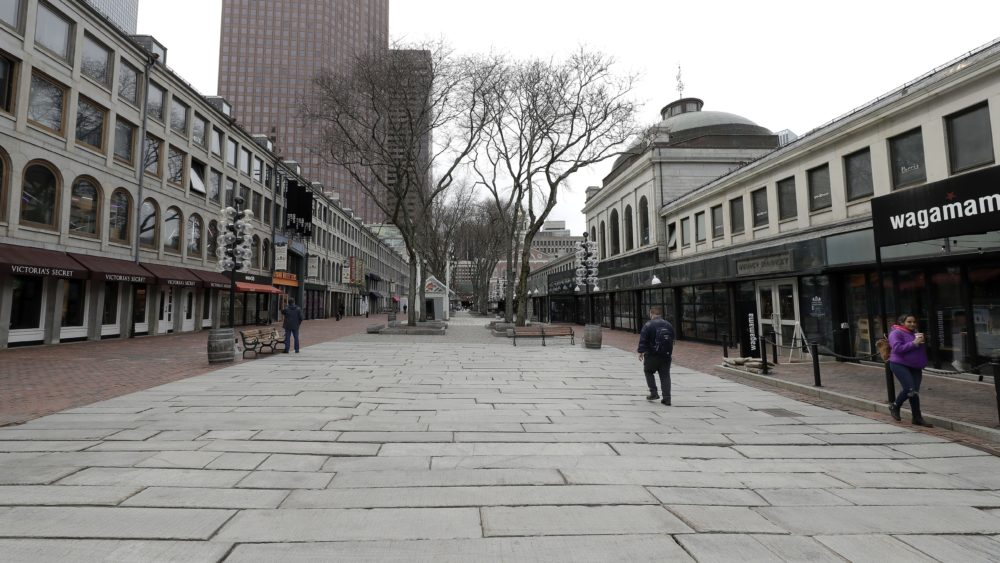 People walk through the nearly empty tourist area of Quincy Market, Wednesday, March 11, 2020, in Boston. (Steven Senne/AP)
