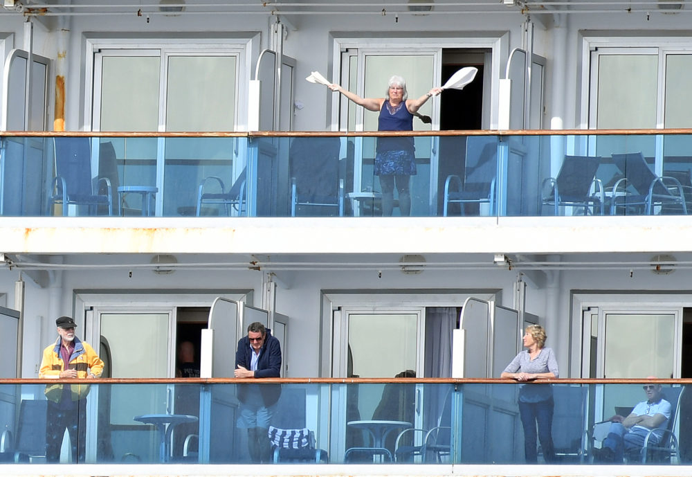 A woman gestures as other people look on from aboard the Grand Princess cruise ship, operated by Princess Cruises, as it maintains a holding pattern about 25 miles off the coast of San Francisco, California on March 8, 2020. (JOSH EDELSON/AFP via Getty Images)