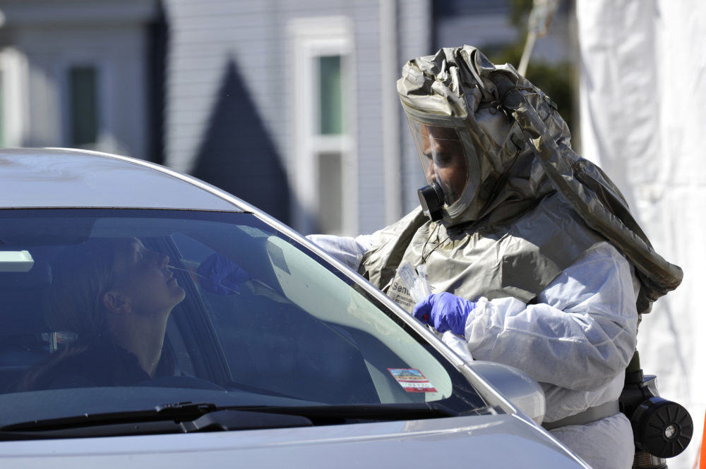 "A medical personnel member takes samples of person at a ""drive-thru"" coronavirus testing lab set up at Somerville Hospital in Somerville, Massachusetts on March 18, 2020. (Joseph Prezioso/AFP via Getty Images)"