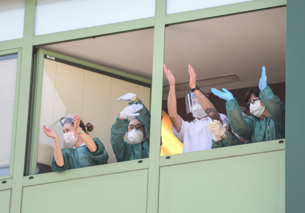 Medical personnel cheers from the windows of a nursing home. (Piero Cruciatti/AFP/Getty Images)