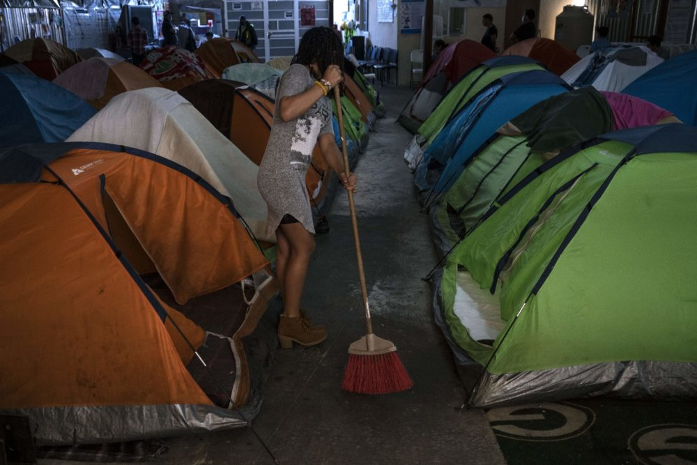 An asylum seeker staying at the Juventud 2000 migrant shelter in Tijuana, Baja California State, Mexico, sweeps the floor on April 3, 2020 as stronger cleaning measures are being implemented to fight the COVID-19 pandemic. (Guillermo Arias/AFP via Getty Images)