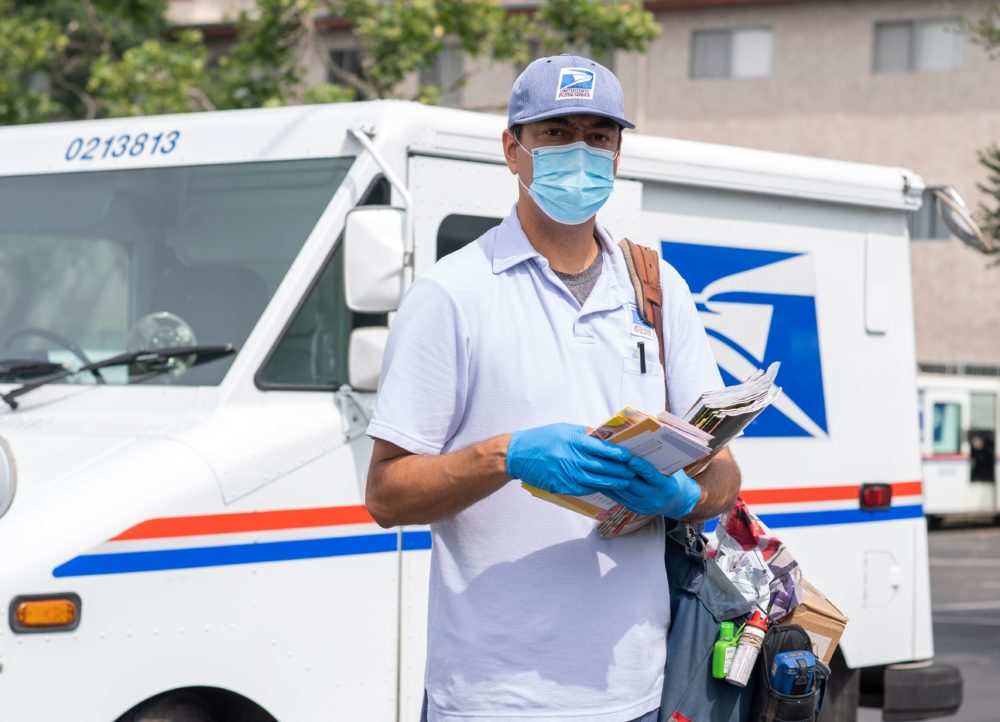 Mail carrier Oscar Osorio poses for a photo before going on his delivery route in Los Feliz amid the Covid 19 pandemic,  April 29, 2020 in Los Angeles, California. (VALERIE MACON/AFP via Getty Images)