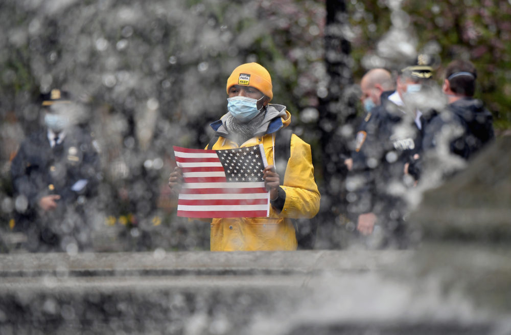 A demonstrator wearing a face mask holds a US flag during a MAGA May Day rally in New York City, on May 1, 2020. (ANGELA WEISS/AFP via Getty Images)