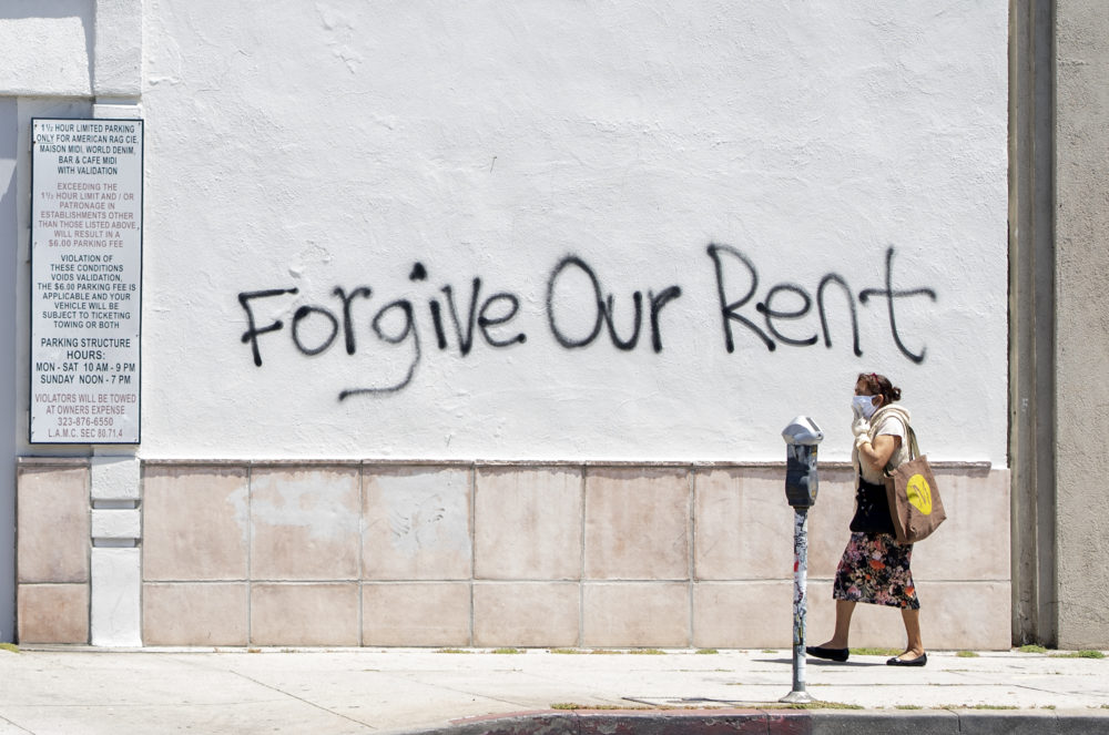 A woman wearing a mask walks past a wall bearing a graffiti asking for rent forgiveness on La Brea Ave on National May Day amid the Covid-19 pandemic,  May 1, 2020, in Los Angeles, California. (VALERIE MACON/AFP via Getty Images)