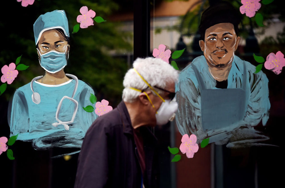 A man wearing a face mask walks past a mural in support of health workers during the outbreak of COVID-19 in Arlington, Virginia, on May 6, 2020. (Olivier Douliery/AFP/Getty Images)