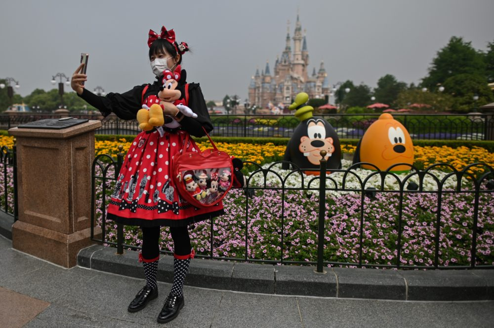 A woman wearing a face mask takes a selfie while visiting the Disneyland amusement park in Shanghai on May 11, 2020. (Hector Retamal/AFP via Getty Images)