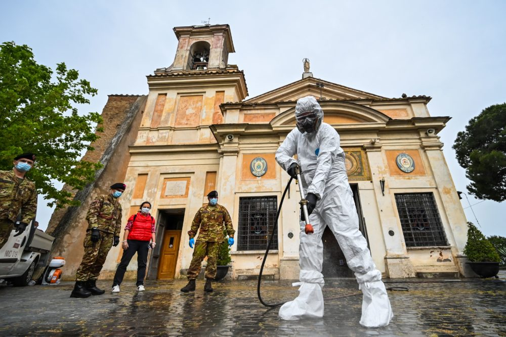 A member of the Italian Army, wearing protective overall and mask, sprays sanitizer outside of the Santuario della Madonna del Divino Amore church on May 13, 2020 in Rome during the country's lockdown. (Andreas Solaro/AFP/Getty Images)