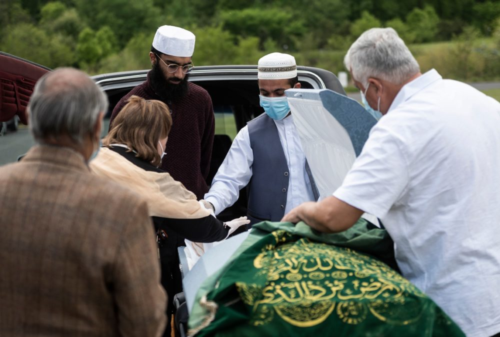 A mourner, wearing a mask and gloves, says her goodbyes after placing dirt in the casket of Ghulam Merzazada at the National Memorial park cemetery in Fairfax, Virginia on May 14, 2020. (ANDREW CABALLERO-REYNOLDS/AFP via Getty Images)