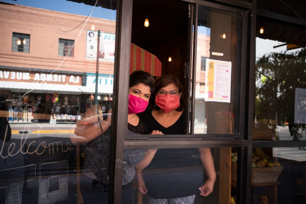 Vanessa Zubia-Meza and her mother Margie Zubia are pictured in the window of their new restaurant called El Paseo on May 18, 2020 in downtown El Paso, Texas. (PAUL RATJE/AFP via Getty Images)