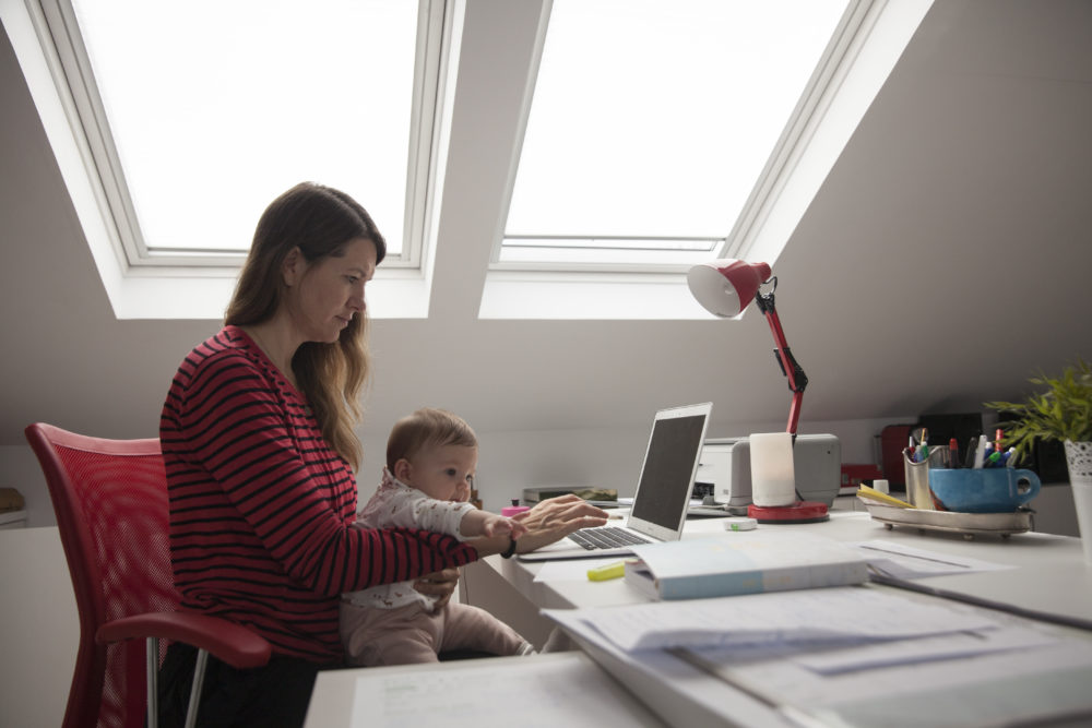 Virginia Bejar, the photographer's partner, strives to work at home while holding her 6-month-old daughter during the COVID-19 lockdown on May 11, 2020, in Majadahonda, Madrid, Spain. (Miguel Pereira/Getty Images)