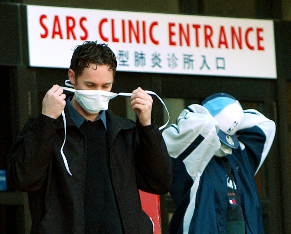 Patients put on face masks as they leave the SARS (Severe Acute Respiratory Syndrome) clinic setup at Sunnybrook & Women's hospital in Toronto, Canada, on 31 March, 2003. (J.P. MOCZULSKI/AFP via Getty Images)