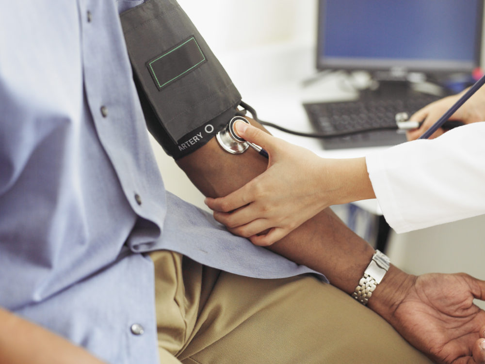 A doctor takes a patient's blood pressure. (Photo/Getty Images)
