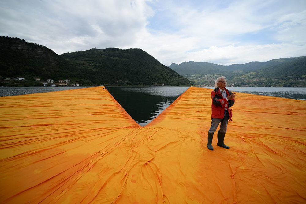"Artist Christo Vladimirov Javacheff walks on his monumental installation ""The Floating Piers"" he created with late Jeanne-Claude, on June 16, 2016, during a press preview at the lake Iseo, northern Italy. Some 200,000 floating cubes create a 3-kilometers runway connecting the village of Sulzano to the small island of Monte Isola on the Iseo Lake for a 16-day outdoor installation opening on June 18. (Filippo Monteforte/AFP/Getty Images)"