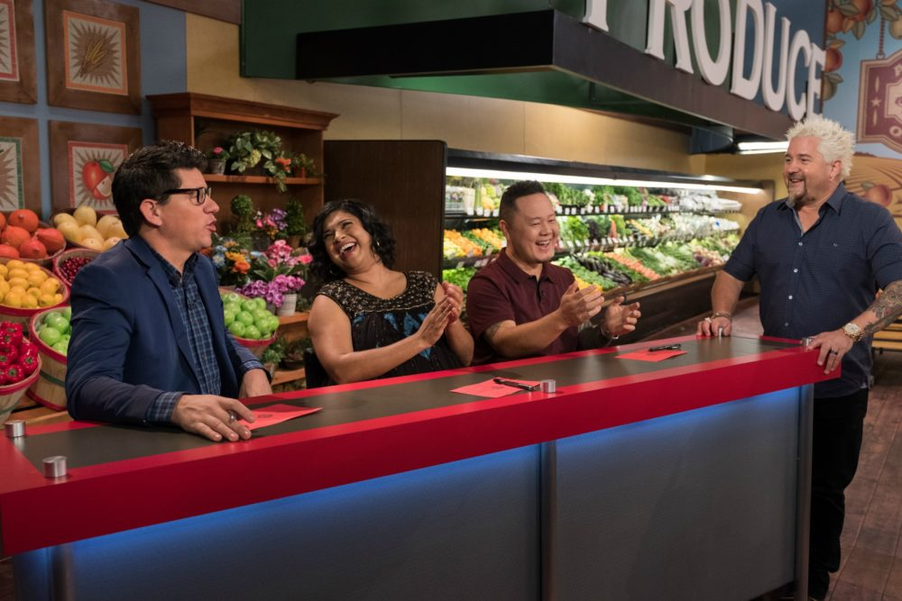 Judges Troy Johnson, Aarti Sequeira, and Jet Tila talk with Host Guy Fieri while the contestants prepare their dishes, as seen on Guy's Grocery Games, Season 14. (Courtesy, Food Network)
