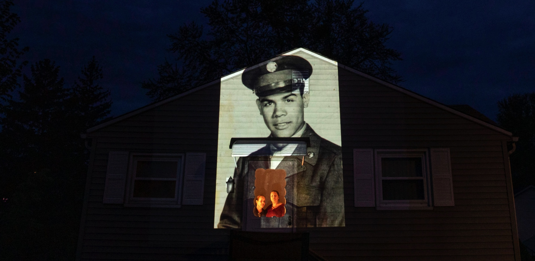 An image of veteran Samuel Melendez is projected onto the home of his nieces, Janet Ramirez, right, and Mary Perez, as they look out a doorway in Chicopee, Mass. (David Goldman/AP)