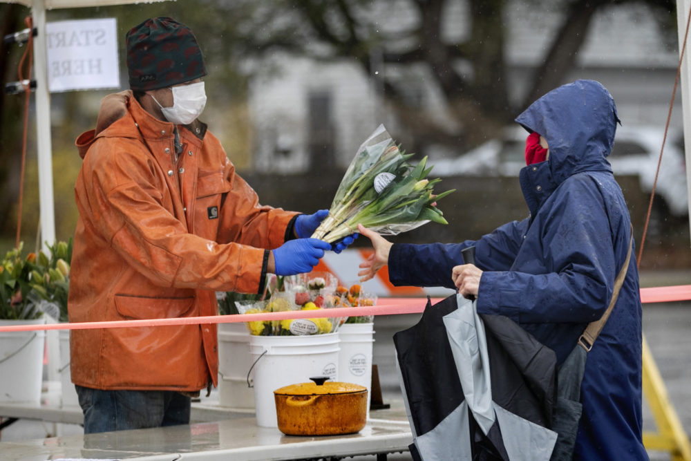 David Baecher sells flowers to a customer at a farmer's market, Friday, May 1, 2020, in Brunswick, Maine. Gov. Janet Mills is requiring that people wear masks in public to help prevent the spread of the coronavirus as part of her business reopening plan. (AP Photo/Robert F. Bukaty)