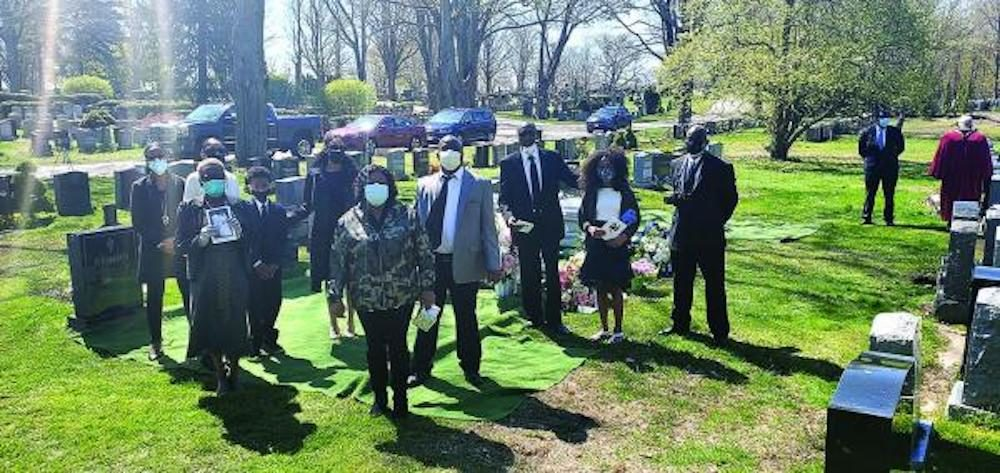 Relatives of Cynthia and Clasford Johnson, who were interred at Cedar Grove Cemetery last weekend, are shown by their grave. Only ten members of the family were allowed to be present at the burial. Photos courtesy Amos Monteiro