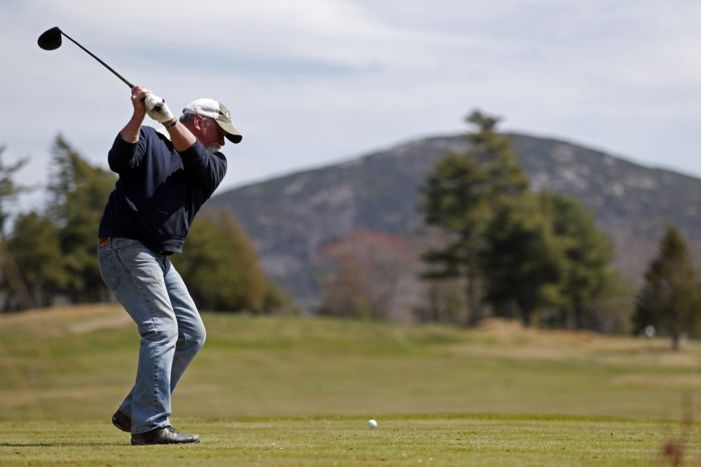 Not far from a mountain in Acadia National Park, background, Jack Gilley hits a tee shot at Kebo Valley Golf Club, Wednesday, May 6, 2020, in Bar Harbor, Maine. Some businesses in the state such as golf courses are reopening to state residents who live in the same county. The roads and facilities of Acadia National Park, however, remain closed.(AP Photo/Robert F. Bukaty)
