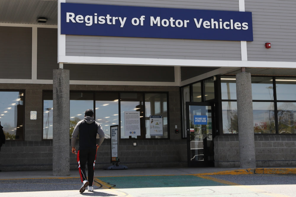A man walks to the Commonwealth of Massachusetts Registry of Motor Vehicles office in Lawrence, Mass., on May 5. (Charles Krupa/AP)