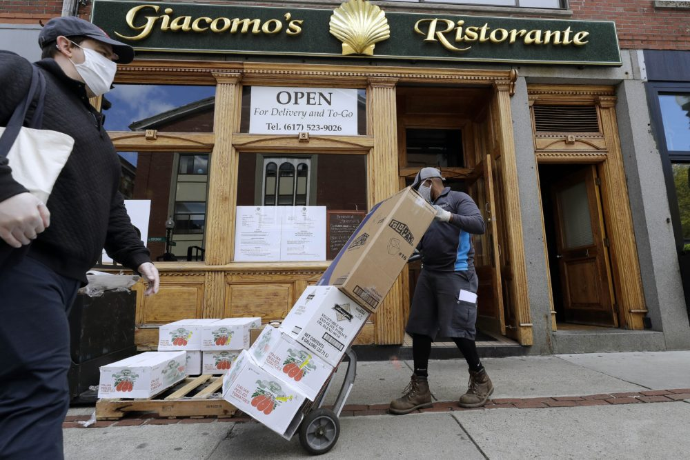 A pedestrian wearing a protective mask passes a food delivery being made to a restaurant providing takeout service during the coronavirus pandemic on May 12 in the North End neighborhood of Boston. (Steven Senne/AP)