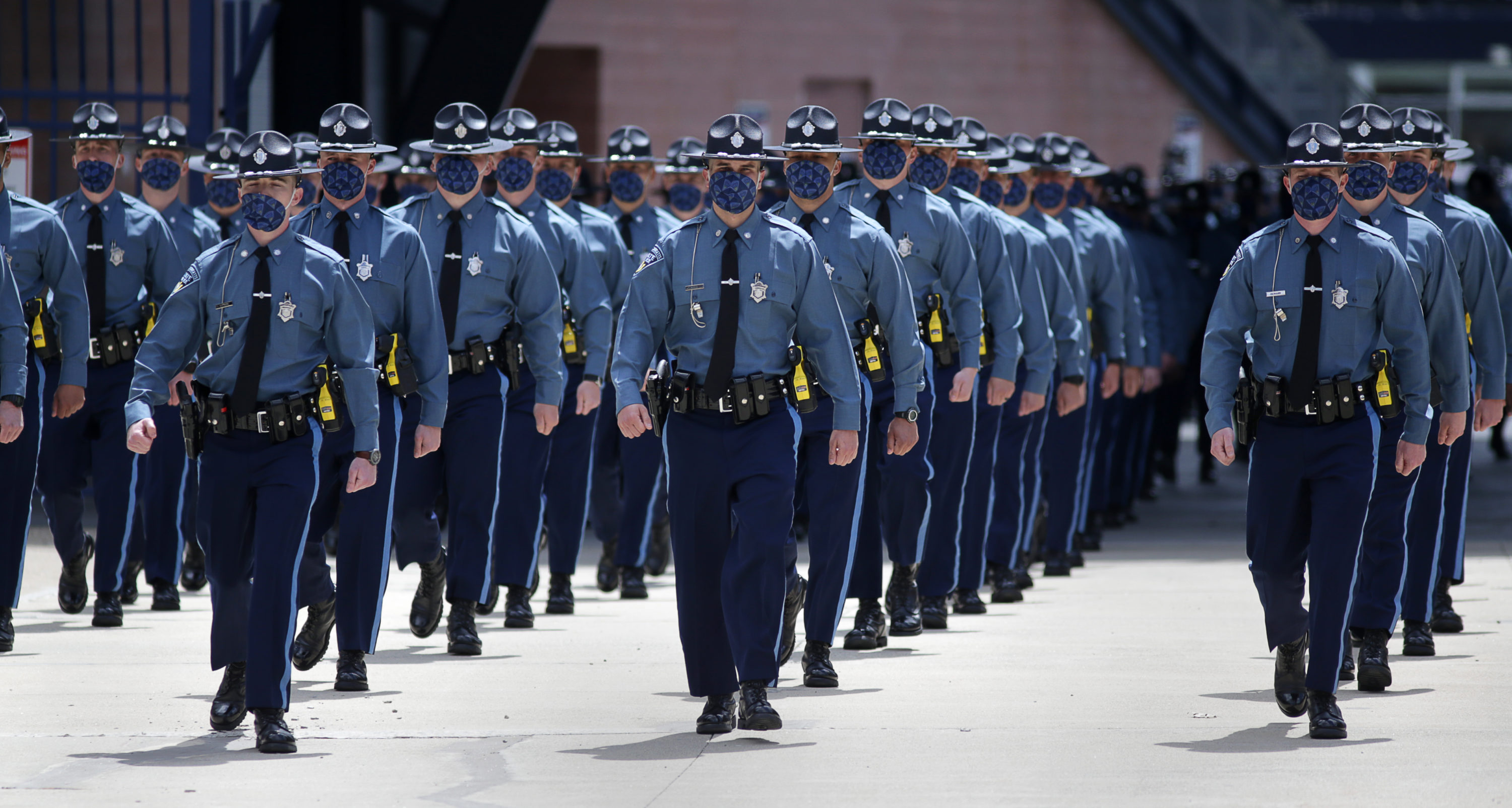 Some of the 240 new Massachusetts State Police troopers as they  marched out of Gillette Stadium after Gov. Charlie Baker swore them in at a graduation ceremony.  (Pool photo/Jonathan Wiggs/The Boston Globe)
