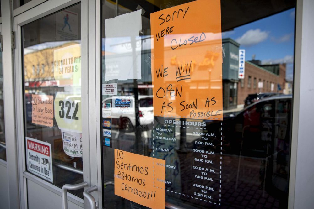 """A sign on the closed Thrift Store on Moody Street, Waltham, says it will be open """"as soon as possible."""" (Robin Lubbock/WBUR)"""