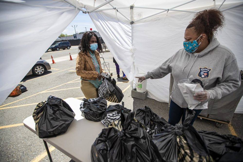 Jennifer Calderon, an advocate at Rosie's Place, assists a woman who's getting bags of groceries and supplies at the food pantry tent. (Jesse Costa/WBUR)