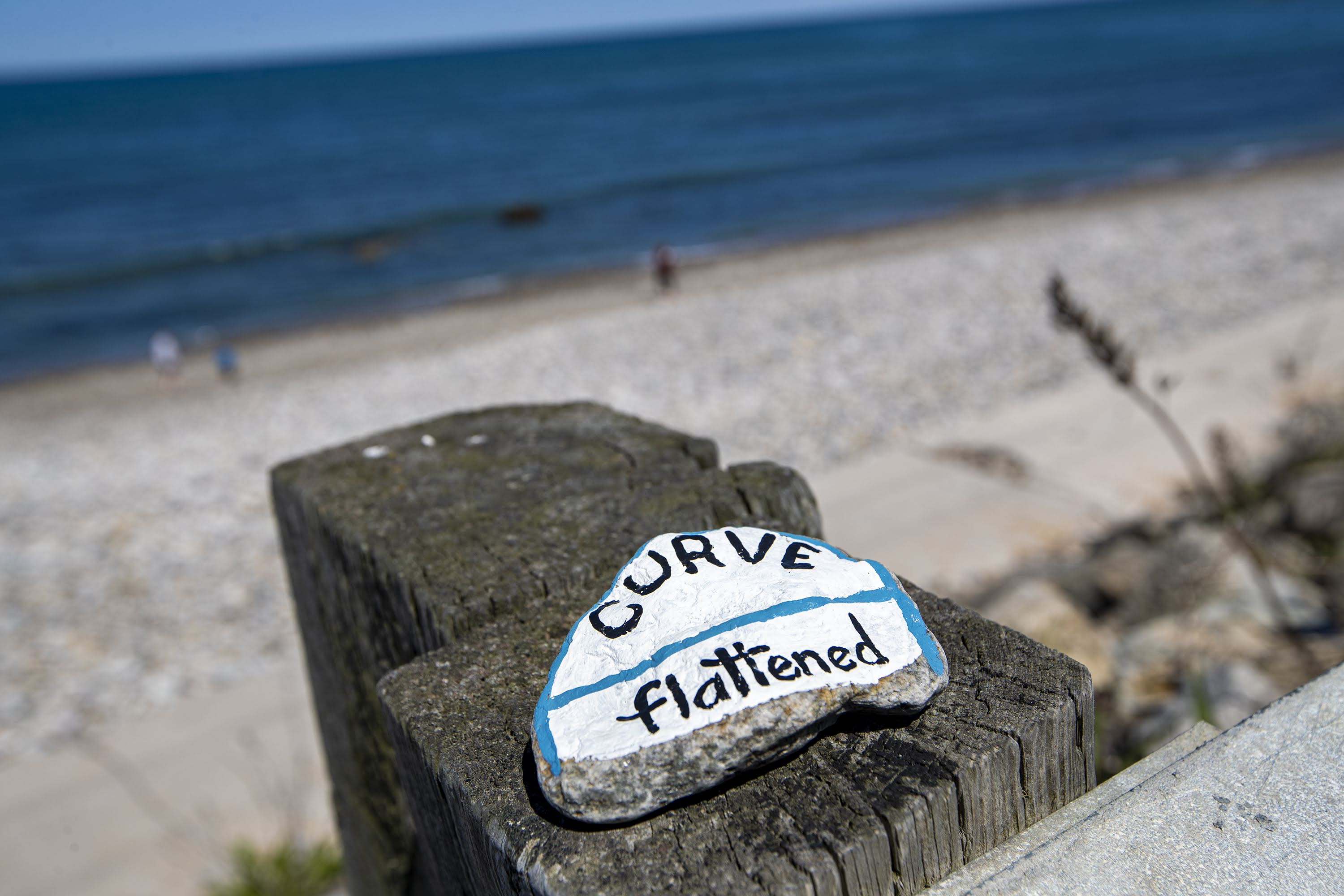 Brightly painted rocks with messages inscribed on them in response to the pandemic are left on top of the guardrails at a virtually empty Brant Rock Beach in Marshfield. (Jesse Costa/WBUR)
