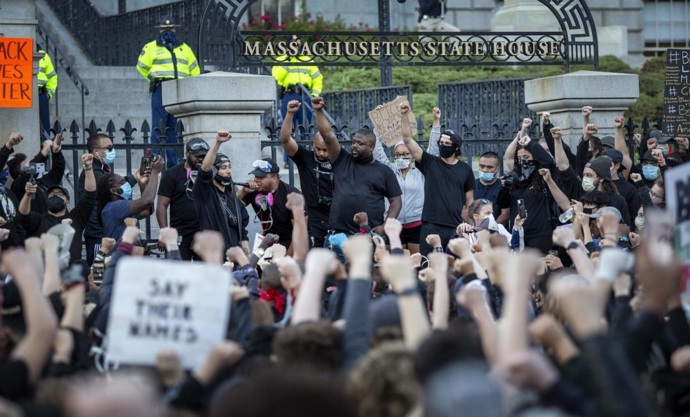 Protesters hold up their fists outside the State House on June 1, 2020. (Robin Lubbock/WBUR)