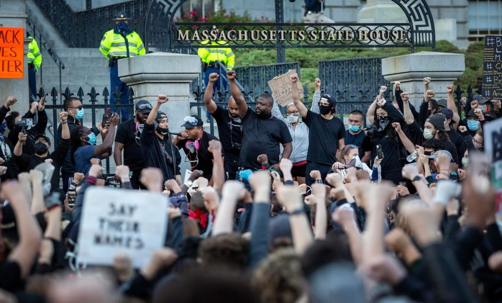 A protesters hold up their fists outside the State House. (Robin Lubbock/WBUR)