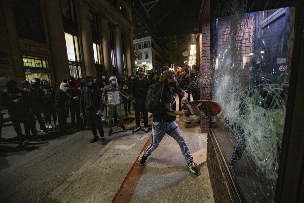 Looters smash a storefront window on School Street after a largely peaceful Black Lives Matter rally at the Massachusetts State House. (Jesse Costa/WBUR)