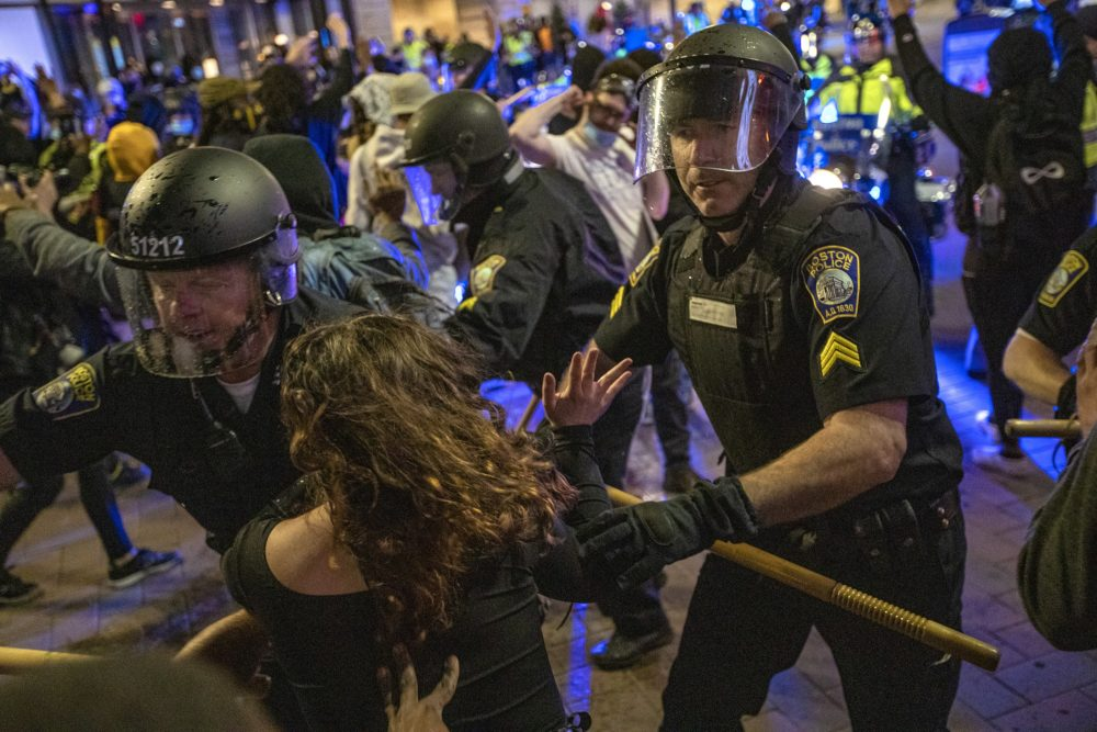 Boston Police move to clear out protesters on Washington Street at Downtown Crossing. (Jesse Costa/WBUR)