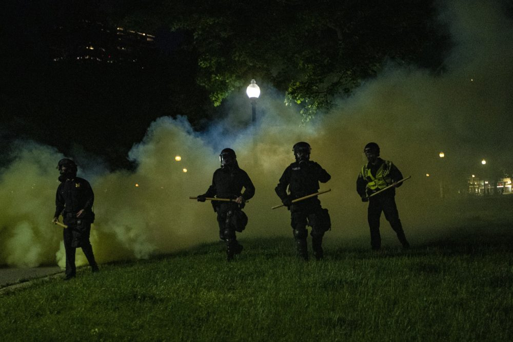 Boston Police emerge from the cloud of tear gas in the Boston Common to clear out protesters. (Jesse Costa/WBUR)