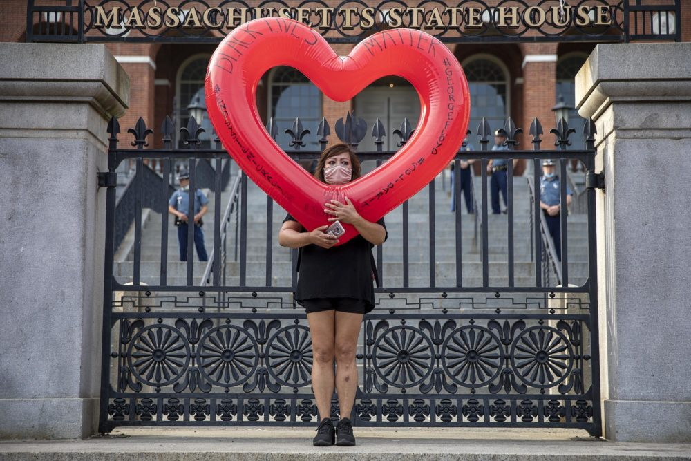 A protester stands at the gates of the Massachusetts State House. (Robin Lubbock/WBUR)